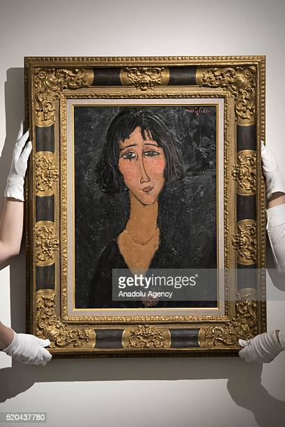 Art handler holds Amedeo Modigliani's Jeune femme a la rose at Christie's on April 11, 2016 in London, England. The work will be sold as part of...