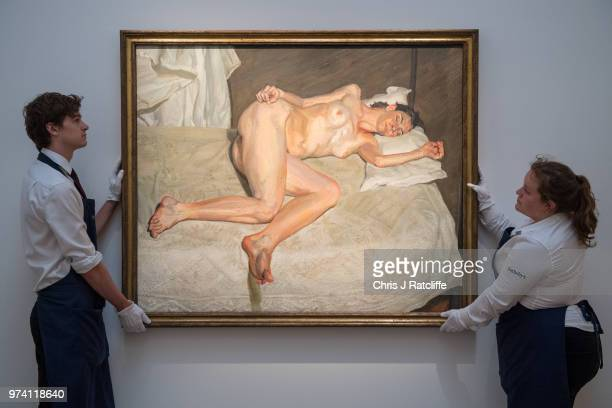 Art handlers adjust 'Portrait on a white cover' by Lucian Freud during a preview of the Contemporary Art sale at Sotheby's on June 14 2018 in London...