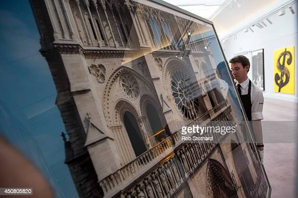 Art handlers carry Thomas Struth's 2000 piece Notre Dame Paris at Sotheby's auction house on June 18 2014 in London England The Sotheby's...