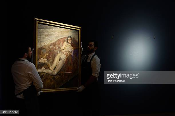 Art handlers hang the painting 'Naked Bella Freud' by artist Lucien Freud on display during the preview ahead of the artist's muse a curated evening...