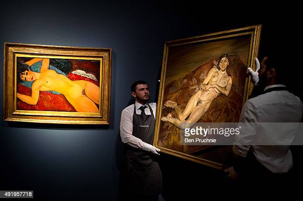 "Art handlers hang the painting ""Naked Bella Freud"" by artist Lucien Freud next to Amedeo Modigliani's 'Nu couche' during the preview ahead of the..."