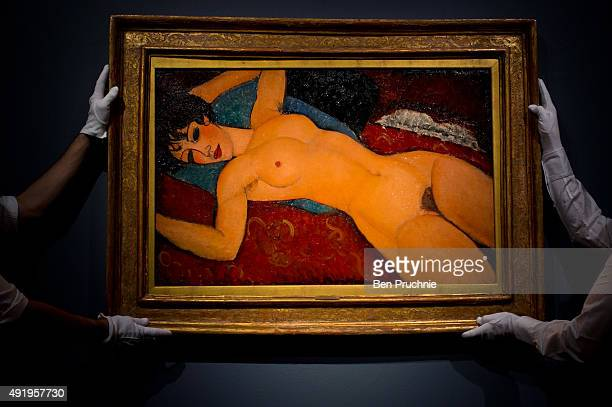 Art handlers hang the painting 'Nu couche' by artist Amedeo Modigliani during the preview ahead of the artist's muse a curated evening sale in...