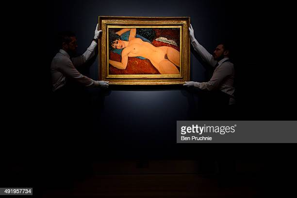 Art handlers hang the painting 'Nu couche' by artist Amedeo Modigliani during the preview ahead of the artist's muse: a curated evening sale in...