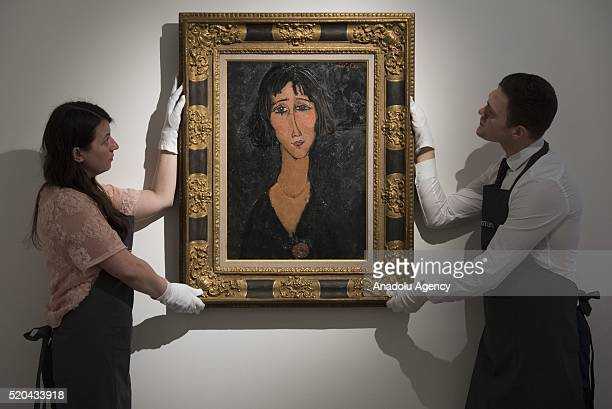 Art handlers hold Amedeo Modigliani's Jeune femme a la rose at Christie's on April 11 2016 in London England The work will be sold as part of...