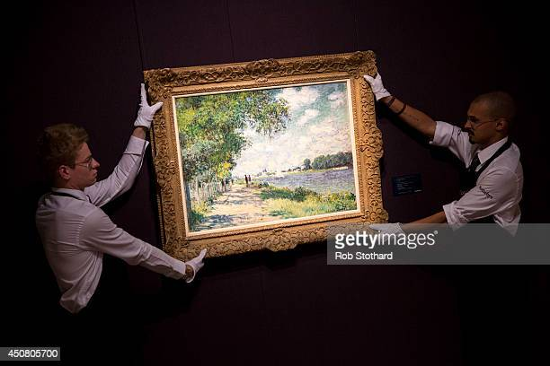 Art handlers pose with Claude Monet's 1875 piece La Siene a Argenteuil, estimated to sell for £7-£10 million, on display at Sotheby's auction house...