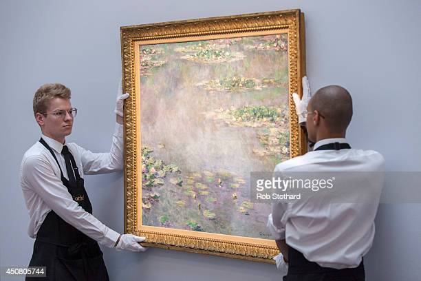 Art handlers pose with Claude Monet's 1906 piece Nympheas estimated to sell for £20£30 million on display at Sotheby's auction house on June 18 2014...