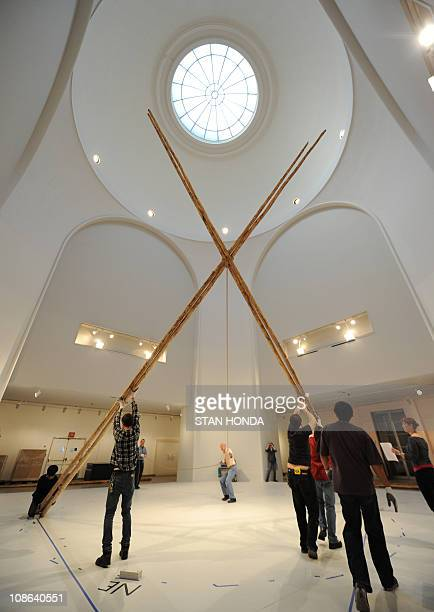 Art handlers raise four poles that will be the frame of a 25foot Blackfeet tipi to be constructed on January 31 2011 at the Brooklyn Museum in the...