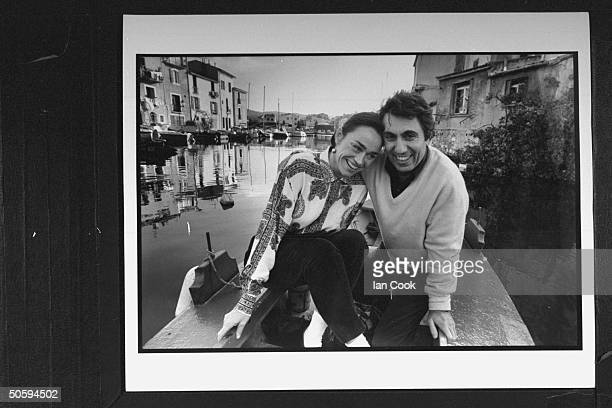 Art lover/boutique owner Francesco Plateroti w his companion Valerie Noizet cuddling in boat at small port lined w houses in Martigues at spot where...