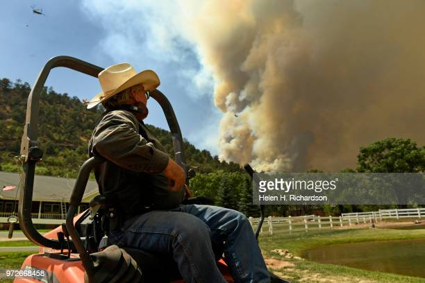 Art Nichols watches helicopters fly by as he mows his lawn along Highway 550 as the large plume of the 416 fire begins to build in the dry afternoon...