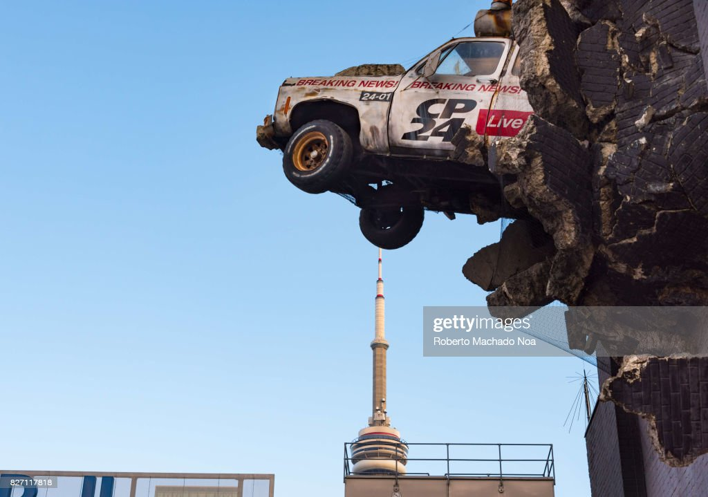 Art of CP24 car though the wall of building, CN tower in background