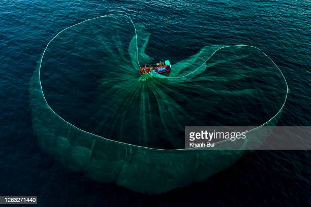 art of fishing net drop on the sea with hard working of the tradition fishermen - life events stock pictures, royalty-free photos & images