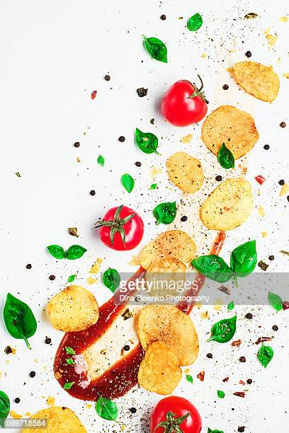 Art of food patterns (with ketchup swoosh, chips, tomatoes and basil leaves )