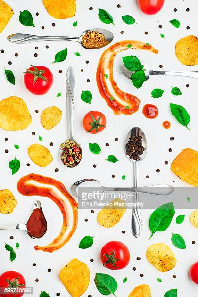 Art of food patterns (with tomato ketchup, chips and basil leaves)