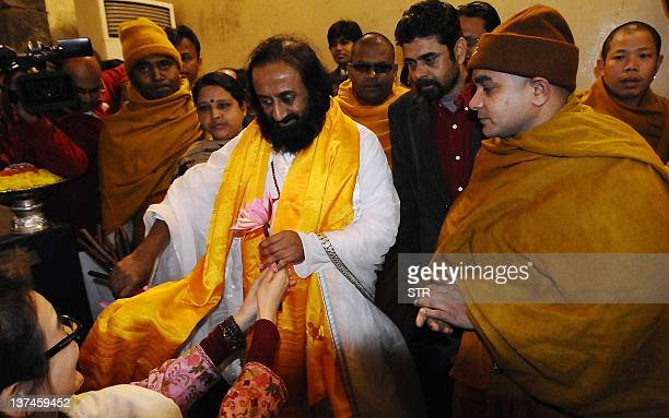 Art of Living Foundation leader Shri Ravi Shankar also known as 'Sri Sri' receives a flotus flower from a supporter as he offers prayers at Mahabodhi...