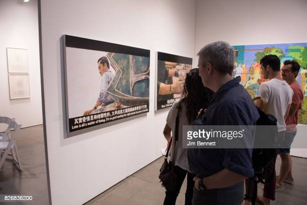 Art patrons examine large paintings by Chow Chun Fe during the Seattle Art Fair at CenturyLink Field on August 5 2017 in Seattle Washington