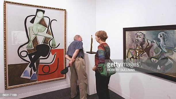 Art patrons view three works by Pablo Picasso Femme dans un Rockingchair Femme debout and Homme assis et centaure 01 December 2005 at Art Basel/Miami...