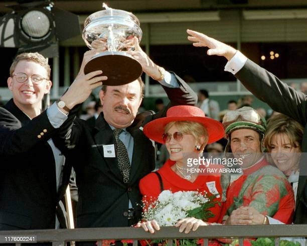 Art Preston owner of Victory Gallop holds the Belmont Stakes trophy as the horse's trainer Elliott Walden and jockey Gary Stevens watch after the...