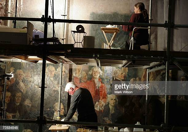 Art restorers on scaffolding work on a wall painting of the founding fathers in a stairwell of the US Capitol November 14 2006 in Washington DC In...