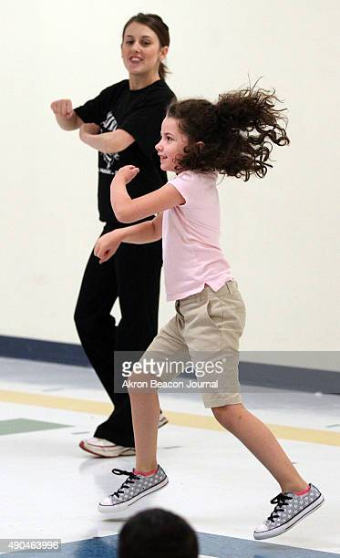 Art Sparks teacher Courtney Thorton dances with third-grader Lyla Senk during the Art Sparks movement class at Harris Elementary School in Akron,...