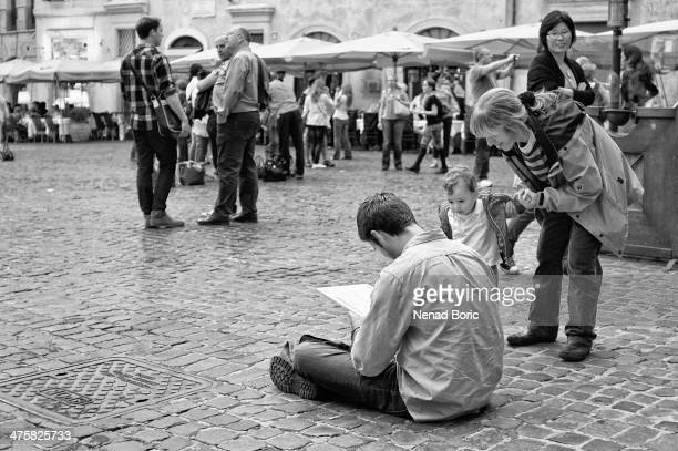 CONTENT] Art student is drawing a picture of Pantheon on Piazza della Rotonda in Rome and attracting children's curiosity