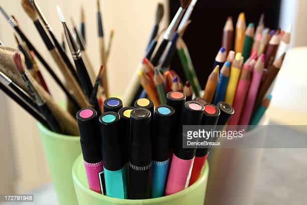 Art supplies filling green cups