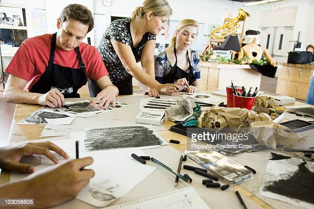 Art teacher assisting students with charcoal drawings