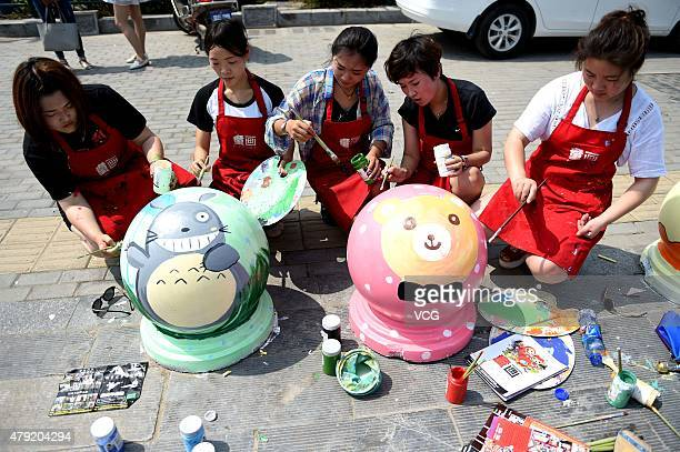 Art teachers paint cartoon characters on stones in front of a shopping mall on July 2 2015 in Bozhou China Five art teachers from a children's studio...
