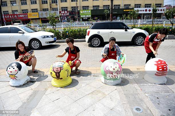 Art teachers paint cartoon characters on stones in front of a shopping mall on July 2 2015 in Bozhou China Five art teachers of a children studio...