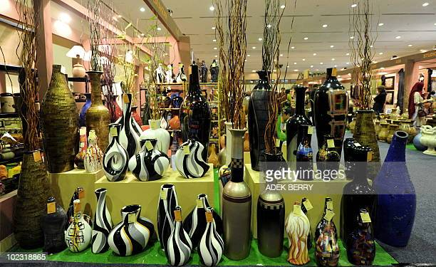 Art works stand as visitors observe items at an exhibition of smalland mediumscale industries in Jakarta on June 23 2010 Smalland mediumscale...