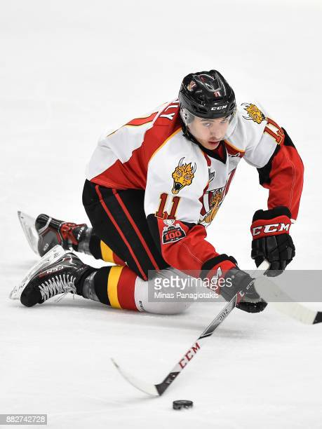 Artagnan Joly of the BaieComeau Drakkar plays the puck as he falls against the BlainvilleBoisbriand Armada during the QMJHL game at Centre...