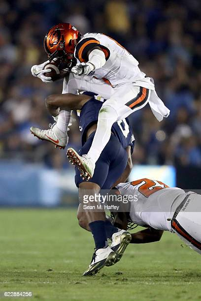 Artavis Pierce of the Oregon State Beavers leaps over Fabian Moreau of the UCLA Bruins during the first half of a game at The Rose Bowl on November...