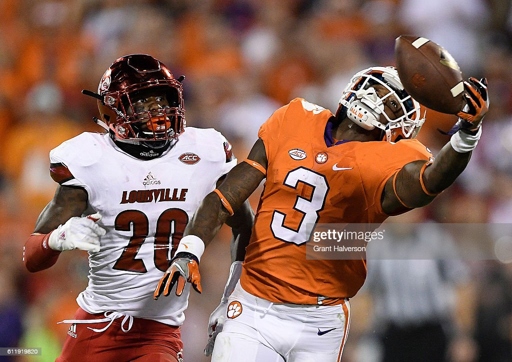 Artavis Scott #3 of the Clemson Tigers attempts to make the catch under pressure from Ronald Walker #20 of the Louisville Cardinals during the fourth quarter at Memorial Stadium on October 1, 2016 in Clemson, South Carolina. The Clemson Tigers defeated the Louisville Cardinals 42-36.