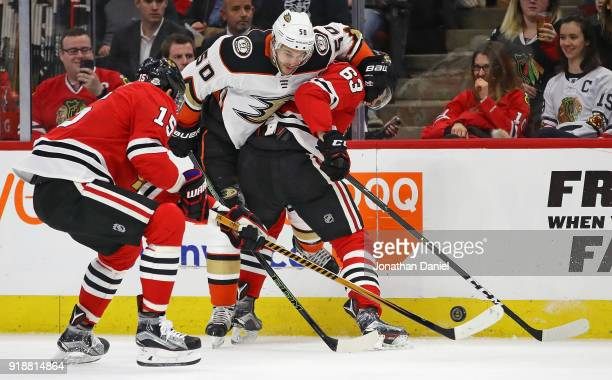 Artem Anisimov and Carl Dahlstrom of the Chicago Blackhawks battle for the puck with Antoine Vermette of the Anaheim Ducks at the United Center on...