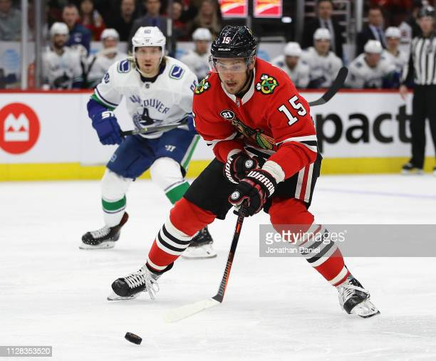 Artem Anisimov of the Chicago Blackhawks advances the puck past Markus Granlund of the Vancouver Canucks at the United Center on February 07 2019 in...