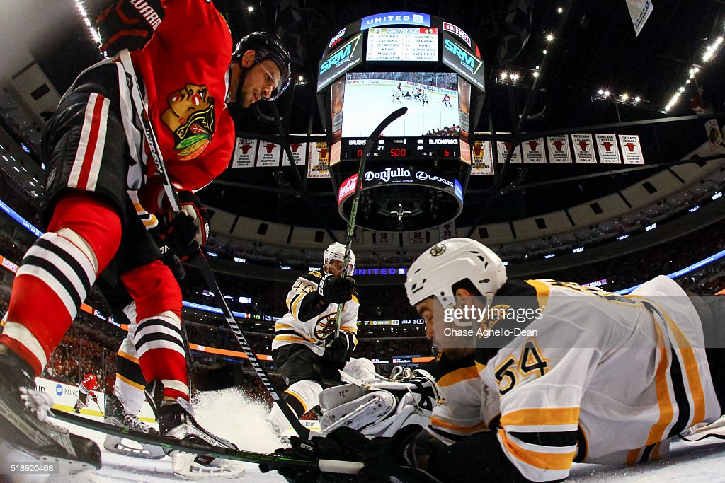 Artem Anisimov #15 of the Chicago Blackhawks and Adam McQuaid #54 of the Boston Bruins battle for the puck during the NHL game at the United Center on April 3, 2016 in Chicago, Illinois.