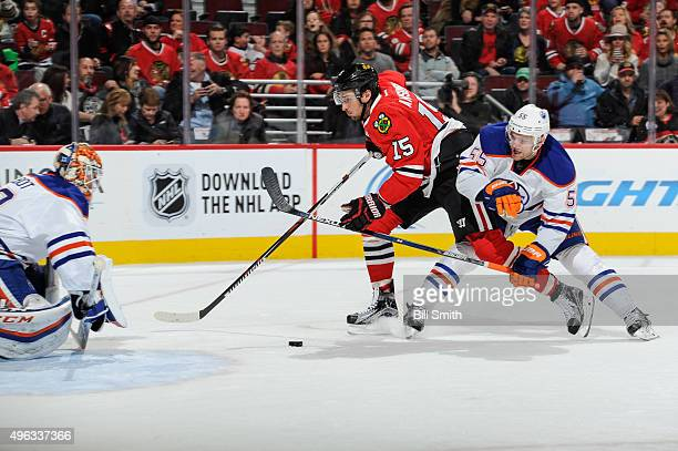 Artem Anisimov of the Chicago Blackhawks and Mark Letestu of the Edmonton Oilers battle for the puck in front of goalie Cam Talbot in the second...