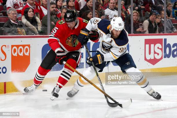 Artem Anisimov of the Chicago Blackhawks and Ryan O'Reilly of the Buffalo Sabres battle for the puck in the first period at the United Center on...