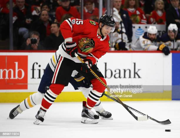 Artem Anisimov of the Chicago Blackhawks controls the puck in front of Ryan O'Reilly of the Buffalo Sabres at the United Center on December 8 2017 in...