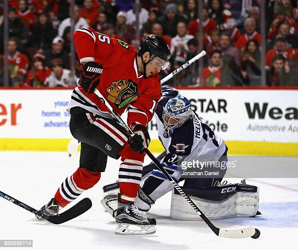 Artem Anisimov of the Chicago Blackhawks gets past Connor Hellebuyck of the Winnipeg Jets to score a second period goal at the United Center on...