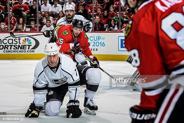 Artem Anisimov of the Chicago Blackhawks watches for the puck in between Rob Scuderi and Drew Doughty of the Los Angeles Kings in the third period of...
