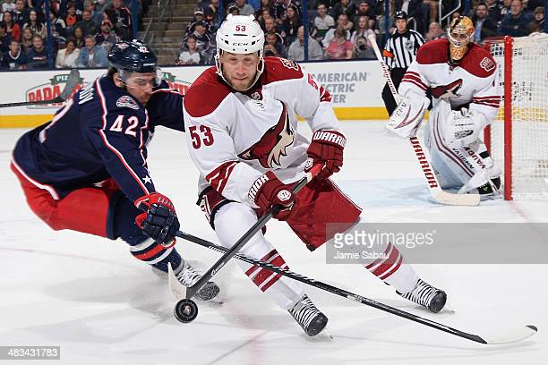 Artem Anisimov of the Columbus Blue Jackets and Derek Morris of the Phoenix Coyotes skate after a loose puck during the first period on April 8, 2014...