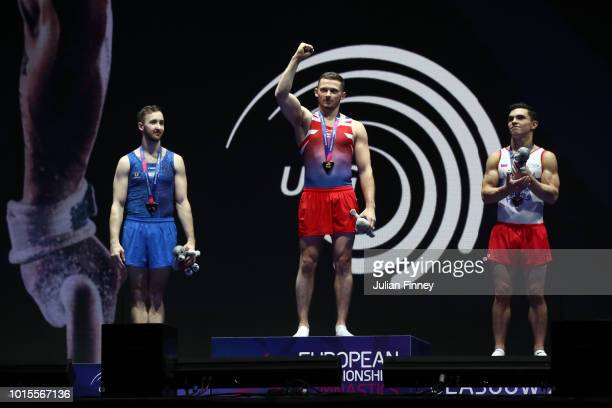 Artem Dolgopyat of Israel and Artur Dalaloyan of Russia looks on as Dominick Cunningham of Great Britain celebrates at the podium after the Floor...