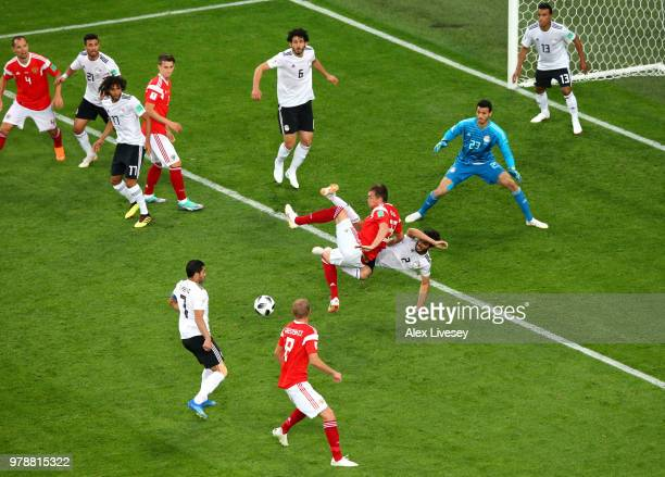 Artem Dzyuba of Russia collides with Ali Gabr of Egypt as he shoots inside the Egypt box during the 2018 FIFA World Cup Russia group A match between...