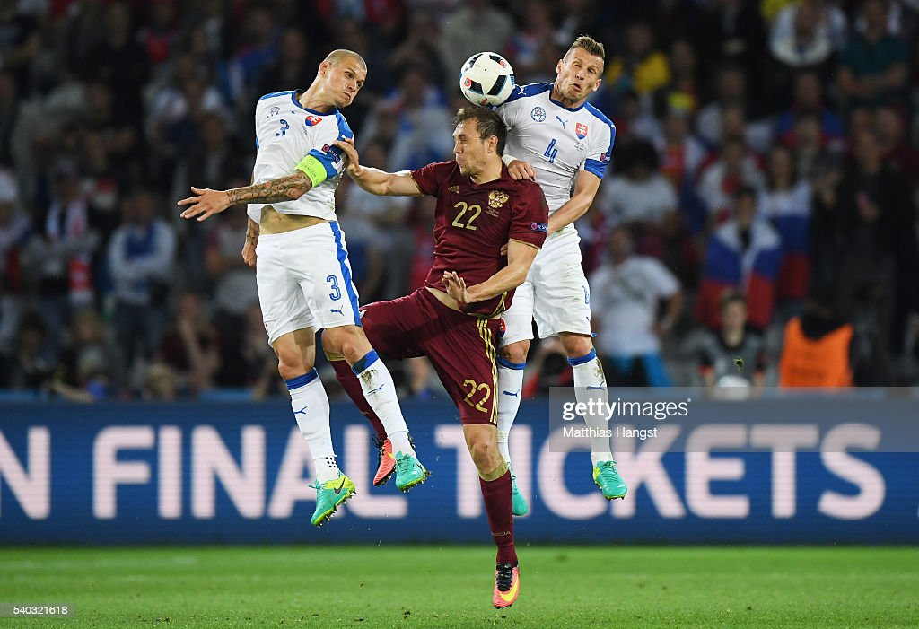 Artem Dzyuba of Russia is tackled in the air by Martin Skrtel and Jan Durica of Slovakia during the UEFA EURO 2016 Group B match between Russia and Slovakia at Stade Pierre-Mauroy on June 15, 2016 in Lille, France.