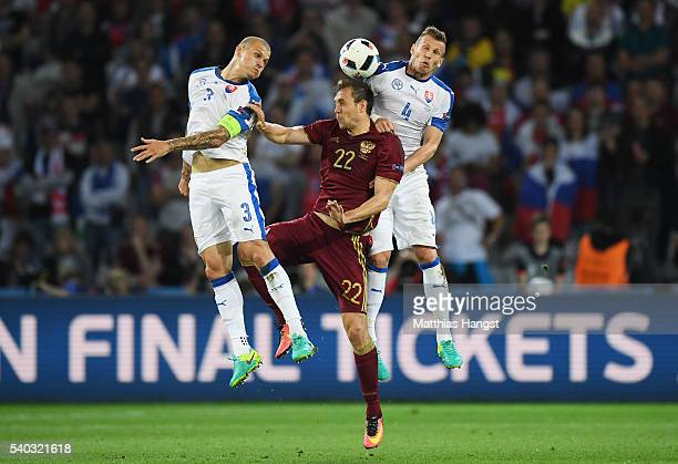 Artem Dzyuba of Russia is tackled in the air by Martin Skrtel and Jan Durica of Slovakia during the UEFA EURO 2016 Group B match between Russia and...