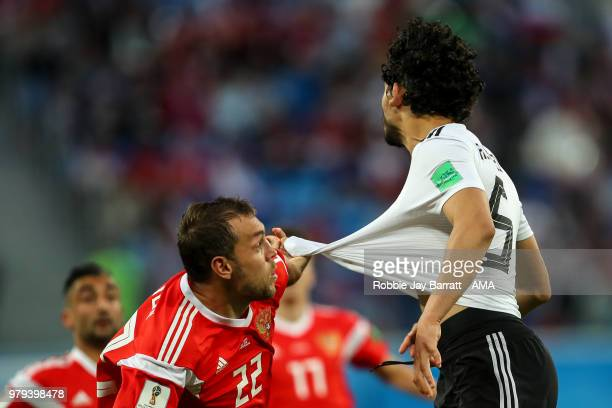 Artem Dzyuba of Russia pulls the shirt of Ahmed Hegazy of Egypt during the 2018 FIFA World Cup Russia group A match between Russia and Egypt at Saint...