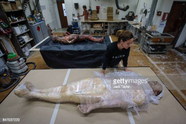 Artem employee Nolwenn Caro poses with a dummy of actor David Thewlis made for the 2015 'Macbeth' film on display during an open evening at the Artem...