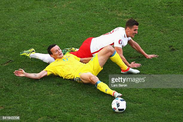 Artem Fedetskiy of Ukraine is tackled by Arkadiusz Milik of Poland during the UEFA EURO 2016 Group C match between Ukraine and Poland at Stade...