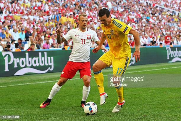 Artem Fedetskiy of Ukraine is tackled by Kamil Grosicki of Poland during the UEFA EURO 2016 Group C match between Ukraine and Poland at Stade...