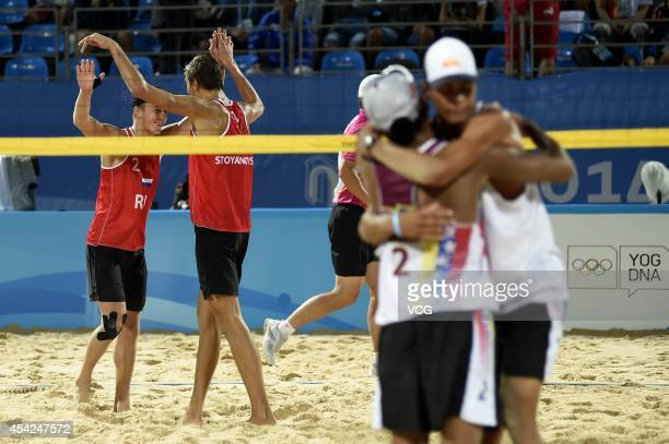 Artem Larzutkin and Oleg Stoyanovskiy of Russia celebrate after beating Jose Gregorio Gomez and Rolando Hernandez of Venezuela in the Men's Beach...